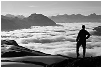 Hiker contemplaing a sea of clouds. Kenai Fjords National Park, Alaska, USA. (black and white)