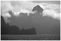 Peak emerging from the fog above bay waters. Kenai Fjords National Park ( black and white)