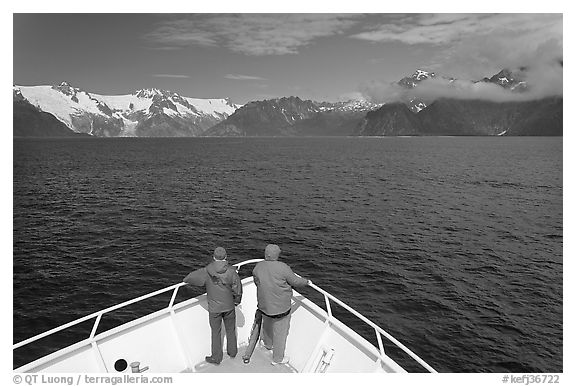 Passengers with red jackets on bow of tour boat, Northwestern Fjord. Kenai Fjords National Park (black and white)