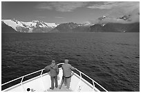 Passengers with red jackets on bow of tour boat, Northwestern Fjord. Kenai Fjords National Park, Alaska, USA. (black and white)