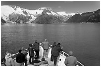 Vistors on bow of tour boat approaching glacier, Northwestern Fjord. Kenai Fjords National Park, Alaska, USA. (black and white)