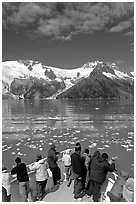 People looking as tour boat slows down for iceberg, Northwestern Fjord. Kenai Fjords National Park, Alaska, USA. (black and white)