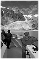 Passengers looking at Northwestern glacier from the deck of tour boat. Kenai Fjords National Park, Alaska, USA. (black and white)