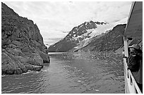 Passenger on small tour boat, island and glacier, Northwestern Fjord. Kenai Fjords National Park, Alaska, USA. (black and white)