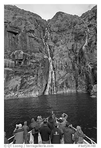 Passengers looking at waterfalls from  bow of tour boat, Cataract Cove. Kenai Fjords National Park (black and white)