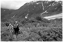 Women with child carrier backpacks on Harding Icefield trail. Kenai Fjords National Park ( black and white)