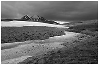 Snow nevesand mountains under dark storm clouds. Lake Clark National Park, Alaska, USA. (black and white)