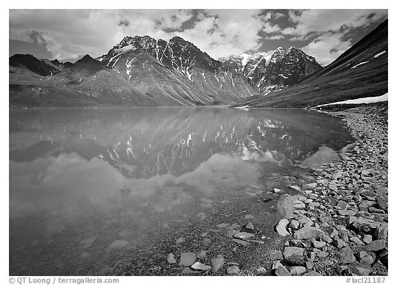 Shore of Turqouise Lake with Telaquana Mountains reflected in silty water. Lake Clark National Park (black and white)