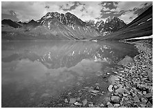 Shore of Turqouise Lake with Telaquana Mountains reflected in silty water. Lake Clark National Park ( black and white)