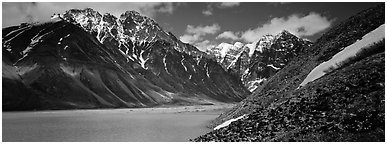 Rugged mountains rising above lake with turquoise waters. Lake Clark National Park (Panoramic black and white)