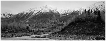 Autumn mountain landscape with snowy peaks above river and trees. Wrangell-St Elias National Park (Panoramic black and white)