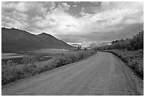 Unpaved McCarthy Road next to lake. Wrangell-St Elias National Park ( black and white)