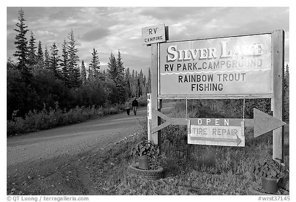 Sign and couple walking on McCarthy road near Silver Lake. Wrangell-St Elias National Park (black and white)