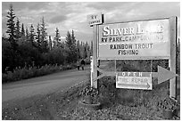 Sign and couple walking on McCarthy road near Silver Lake. Wrangell-St Elias National Park ( black and white)