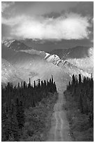 Road leading to mountains and clould lit by sunset light. Wrangell-St Elias National Park, Alaska, USA. (black and white)
