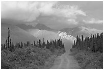 Gravel road leading to mountains lit by sunset light. Wrangell-St Elias National Park, Alaska, USA. (black and white)