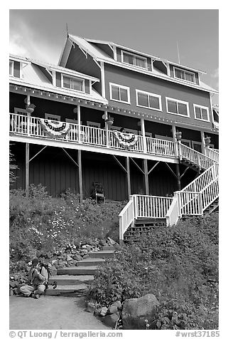 Hiker sitting on steps of Kennicott Lodge. Wrangell-St Elias National Park (black and white)