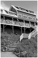 Hiker sitting on steps of Kennicott Lodge. Wrangell-St Elias National Park, Alaska, USA. (black and white)