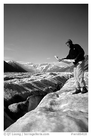 Hiker checks map on Root Glacier. Wrangell-St Elias National Park (black and white)