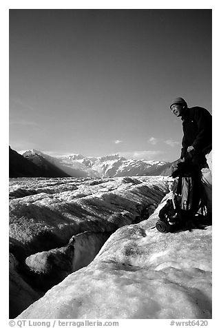 Hiker reaches for item in backpack on Root Glacier. Wrangell-St Elias National Park (black and white)