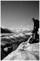 Hiker reaches for item in backpack on Root Glacier. Wrangell-St Elias National Park, Alaska, USA. (black and white)
