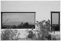Shrubs, Chisos mountains, Persimmon Gap Visitor Center window reflexion. Big Bend National Park, Texas, USA. (black and white)