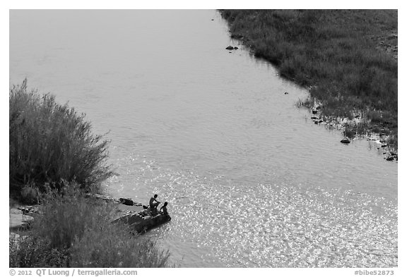 Couple sitting on edge of hot springs seen from above. Big Bend National Park (black and white)