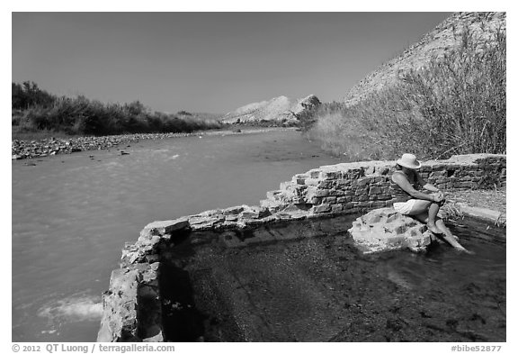 Tourist sitting in hot springs next to river. Big Bend National Park (black and white)
