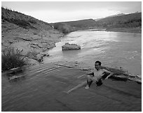 Visitor relaxes in hot springs next to Rio Grande. Big Bend National Park ( black and white)