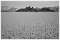 Tiles in cracked mud and Grand Stand, Racetrack playa, dusk. Death Valley National Park, California, USA. (black and white)