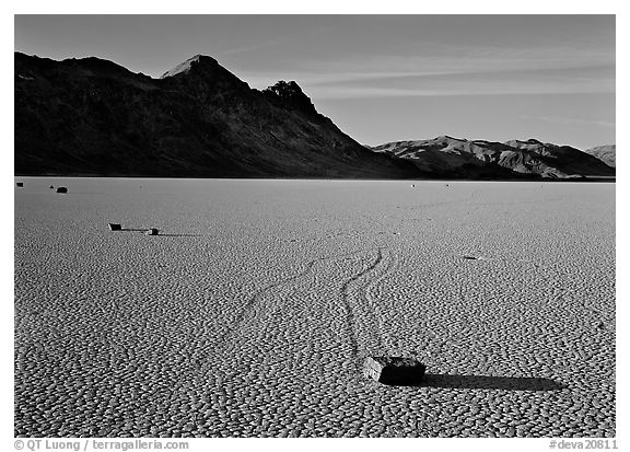 Tracks, moving stone on Racetrack playa and Ubehebe Peak, late afternoon. Death Valley National Park (black and white)