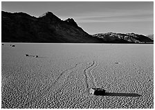 Tracks, moving stone on Racetrack playa and Ubehebe Peak, late afternoon. Death Valley National Park ( black and white)