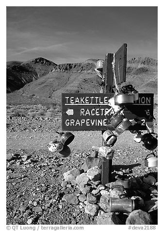Teakettle Junction sign, adorned with teakettles. Death Valley National Park (black and white)
