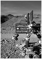 Teakettle Junction sign, adorned with teakettles. Death Valley National Park ( black and white)