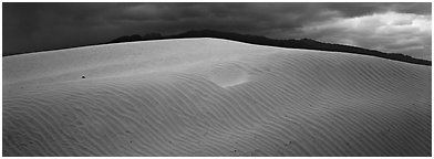 Dune and mountain in stormy weather. Death Valley National Park (Panoramic black and white)