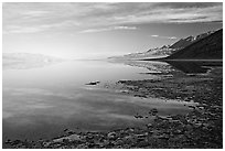 Flooded Badwater basin and Black mountain reflections, early morning. Death Valley National Park, California, USA. (black and white)