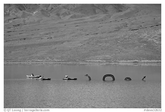 Kayakers approaching the dragon in the rare Manly Lake. Death Valley National Park (black and white)
