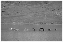 Kayakers approaching the dragon in the rare Manly Lake. Death Valley National Park, California, USA. (black and white)