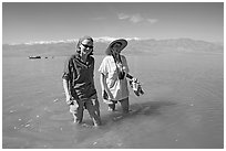 Women wading in the knee-deep seasonal lake. Death Valley National Park, California, USA. (black and white)