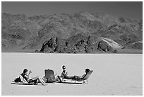 Tourists sunning themselves with beach chairs on the Racetrack. Death Valley National Park, California, USA. (black and white)