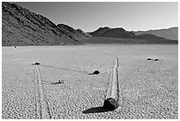 Moving rocks and non-linear tracks, the Racetrack. Death Valley National Park, California, USA. (black and white)