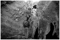 Hikers climbing in a narrow side canyon. Death Valley National Park ( black and white)