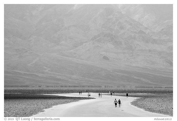 Tourists walking onto Salt Pan at Badwater. Death Valley National Park (black and white)