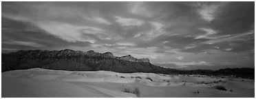 White sand dunes, mountain range, and colorful clouds. Guadalupe Mountains National Park (Panoramic black and white)