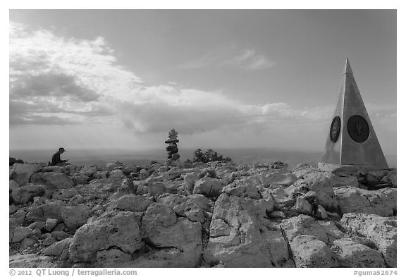 Hiker sitting on Guadalupe Peak summit with cairn and monument. Guadalupe Mountains National Park (black and white)