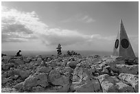 Hiker sitting on Guadalupe Peak summit with cairn and monument. Guadalupe Mountains National Park ( black and white)