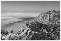 Hiker surveying view from Guadalupe Peak. Guadalupe Mountains National Park, Texas, USA. (black and white)