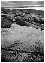 View over Atlantic from top of Mt Cadillac with granite slab covered with lichen. Acadia National Park, Maine, USA. (black and white)