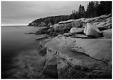 Granite slabs and Otter Point at sunrise. Acadia National Park, Maine, USA. (black and white)