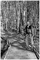 Hiker with backpack standing on boardwalk. Congaree National Park, South Carolina, USA. (black and white)